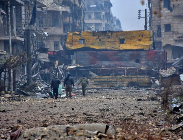 Forças leais ao governo sírio caminham pelo bairro de Bustan al-Qasr, em Aleppo, após capturar a área, na Síria