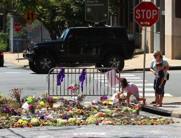 Criança deixa flores na rua onde uma pessoa foi morta após carro avançar em multidão durante protesto contra ato de supremacistas brancos, em Charlotteville, Virgínia, EUA