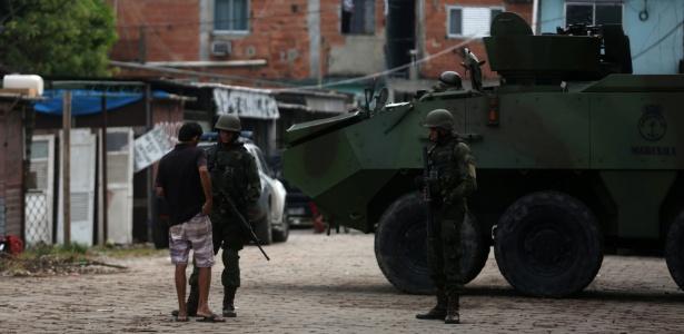 """20.fev.2018 - Morador da favela Kelson""""s, na zona norte do Rio de Janeiro, mostra documentos aos militares. Estado do Rio está sob intervenção - Pilar Olivares/Reuters"""