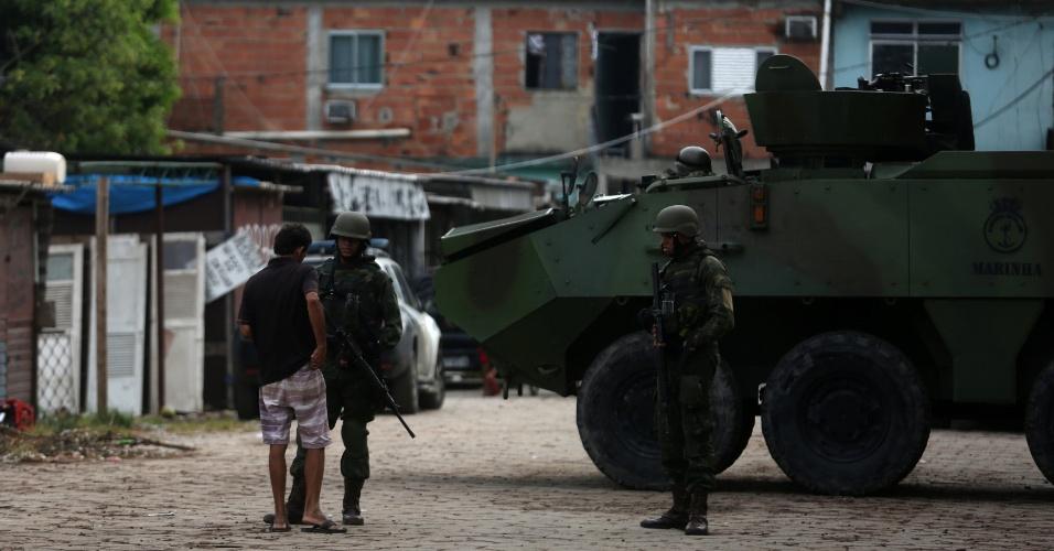 20.fev.2018 - Morador da favela Kelson's, na zona norte do Rio de Janeiro, mostra documentos aos militares. Apenas um muro separa a comunidade dominada pelo Comando Vermelho do CIAA (Centro de Instrução Almirante Alexandrino), da Marinha