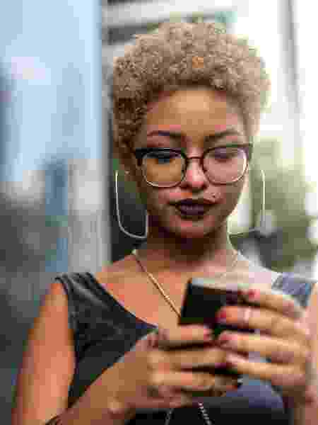Moça usando celular - iStock - iStock