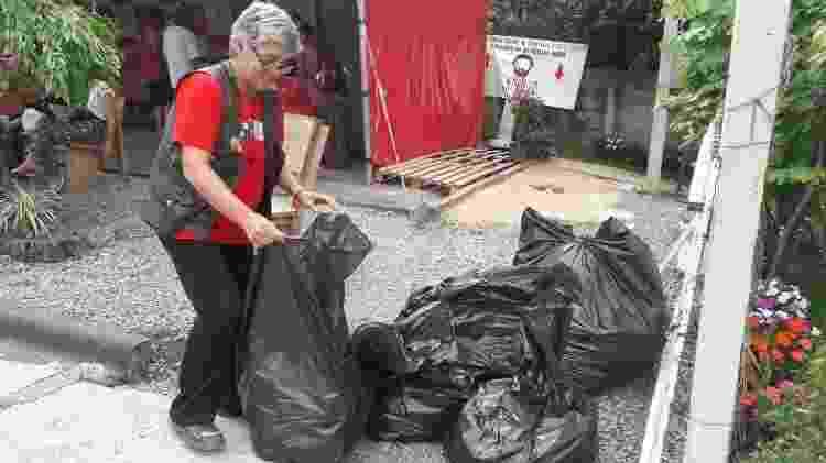 Militante recolhe lixo no local onde estava instalada a Vigília Lula Livre - Vinícius Konchinski/UOL - Vinícius Konchinski/UOL