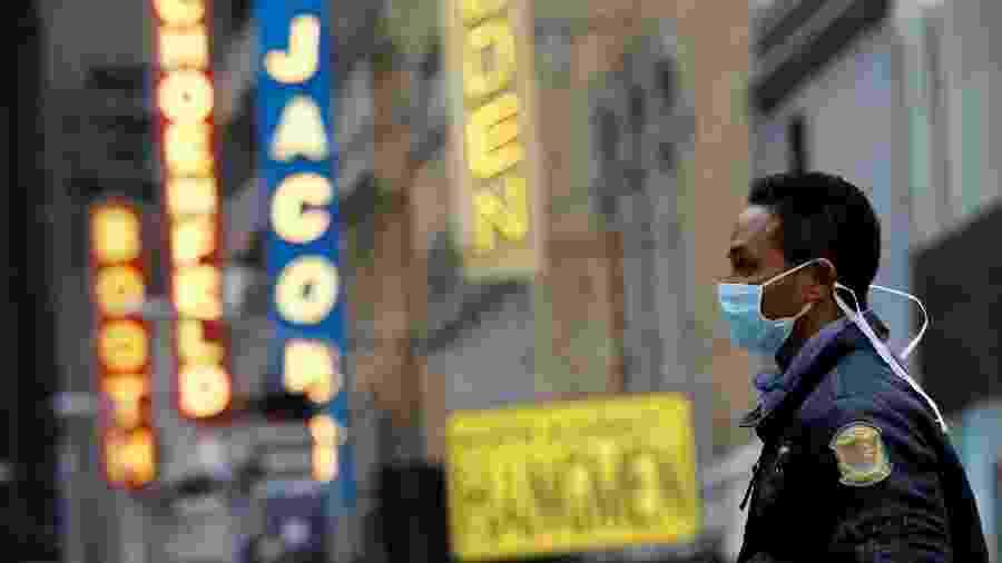 12.mar.2020 - Homem usando máscara caminha pela Broadway após anúncio de cancelamentos por causa do coronavírus - Andrew Kelly/Reuters