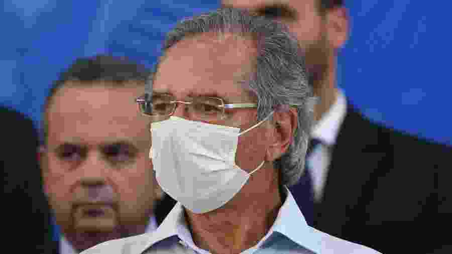 24.abr.2020 - De máscara, o ministro da Economia, Paulo Guedes, acompanha pronunciamento do presidente Jair Bolsonaro (sem partido) - Edu Andrade/Fotopress/Estadão Conteúdo