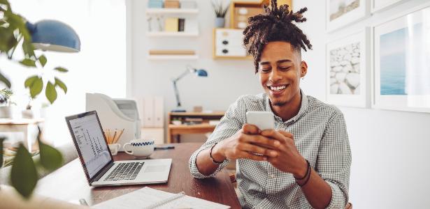 jovem negro, celular, computador, investimentos, economia