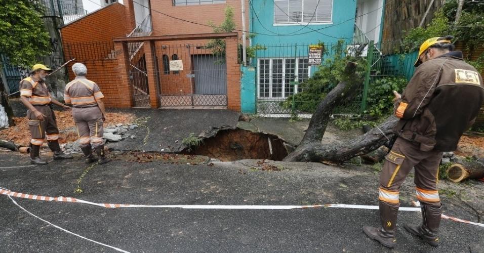"""15.jan.2016 - Uma cratera se formou na calçada da rua Fradique Coutinho, na zona oeste de São Paulo, após o rompimento de uma tubulação subterrânea de água e esgoto que passa pela região. Agentes da CET (Companhia de Engenharia de Tráfego) interditaram a rua e retiraram um árvore que foi """"engolida"""" pelo buraco no momento do acidente"""
