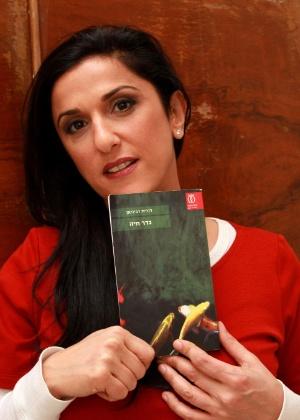 """A autora israelense Dorit Rabinyan posa com seu livro """"Gader Haya"""", em Tel Aviv, que fala do amor entre uma israelense e um palestino"""