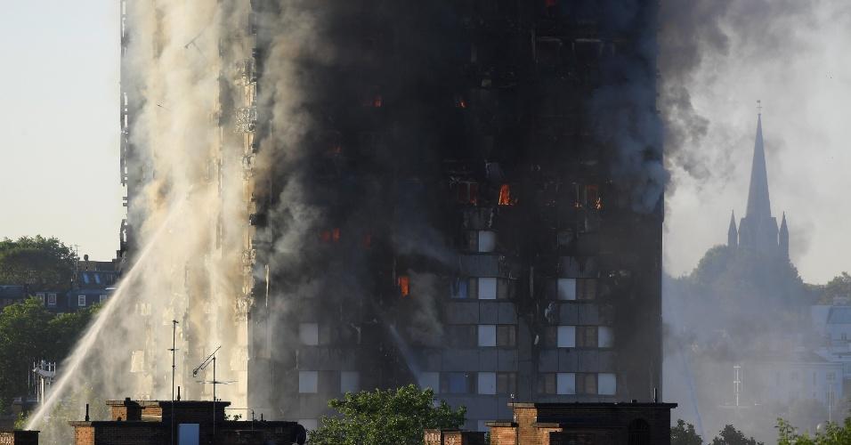14.jun.2017 - Bombeiros combatem chamas em prédio. Quarenta carros e ao menos 200 homens são empregados no trabalho iniciado por volta da 1h30 no horário local