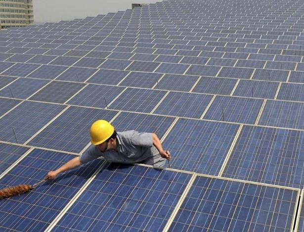 Funcionário limpa painéis de energia solar na China; governo do país está subsidiando produtores de energia renovável - REUTERS