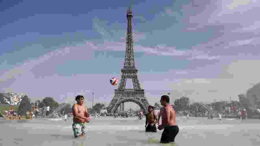29.jun.2019 - Jovens brincam em fonte próxima à Torre Eiffel durante onda de calor em Paris - Zakaria Abdelkafi/AFP