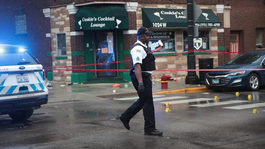 Policiais isolam área para analisar local alvo dos disparos que deixaram 14 pessoas feridas em funeral nos EUA - Scott Olson/Getty Images/AFP