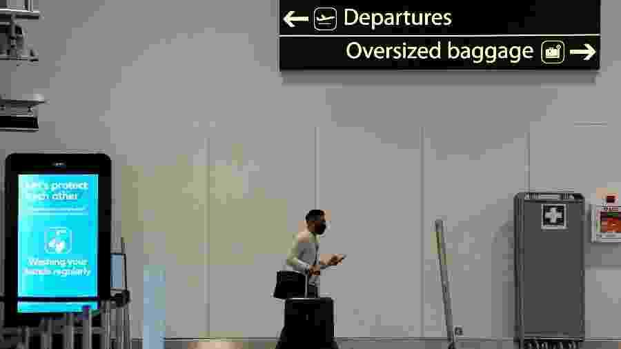 Passageiro usa máscara de proteção no aeroporto de Gatwick, no Reino Unido - Toby Melville/Reuters