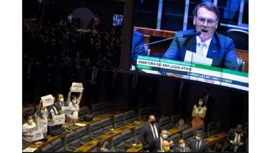 """Bolsonaro no telão da Câmara enquanto discursa em sessão conjunta do Congresso e protesto dos deputados do PSOL: """"fascista e genocida"""" - EFE"""
