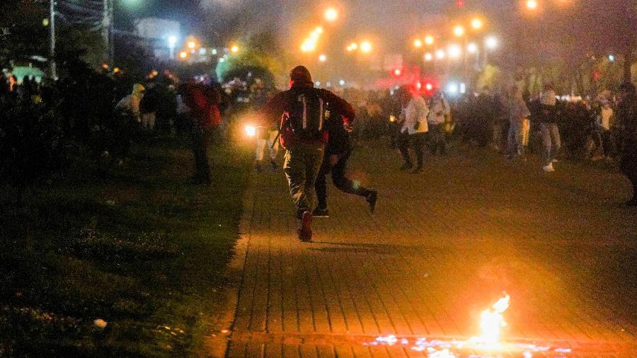 Manifestantes correm enquanto gás lacrimogêneo cai durante um protesto em Bogotá, Colômbia - Nathalia Angarita/Reuters