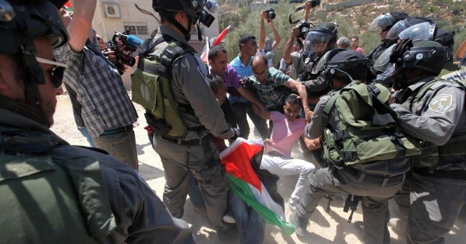 30.ago.2015 - Palestinos entram em confronto com soldados israelenses após escavadeiras militares arrancarem oliveiras para abrir caminho para a construção da barreira de separação de Israel, na cidade do banco ocidental de Beit Jala, perto do assentamento judaico de Gilo, na Cisjordânia