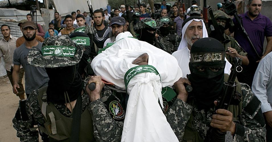 10.out.2015 - Militantes palestinos da brigada Ezzedine al-Qassam, braço armado do Hamas, carregam o corpo de um manifestante palestino de 22 anos, Jihad al-Obeid, que morreu em confrontos com as forças de segurança israelenses perto da fronteira, durante seu funeral em Deir al -Balah, no centro da faixa de Gaza. A violência entre israelenses e palestinos subiu nos últimos dias após uma nova escalada de confrontos na região