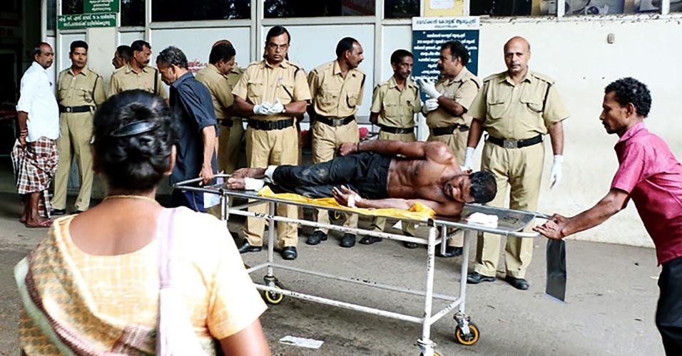 10.abr.2016 - Vítima é resgatada e levada a hospital após incêndio em um templo hindu de Kollam, no sul da Índia. A tragédia provocou pelo menos cem mortes. De acordo com as autoridades locais, 350 pessoas se feriram no local, que pegou fogo após uma explosão causada por uma faísca de um artefato explosivo