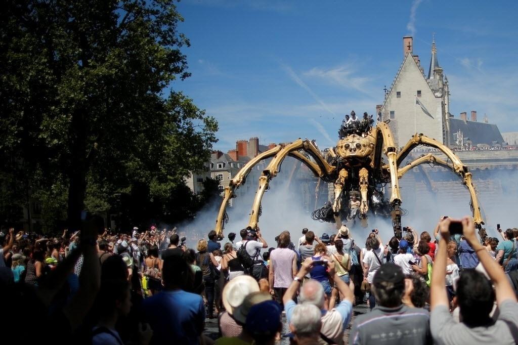 8.jul.2016 - Público tira fotos e assiste apresentação de uma aranha mecânica gigante chamada de Kumo Ni, criada pela empresa de produção La Machine, no meio de uma praça em Nantes, na França