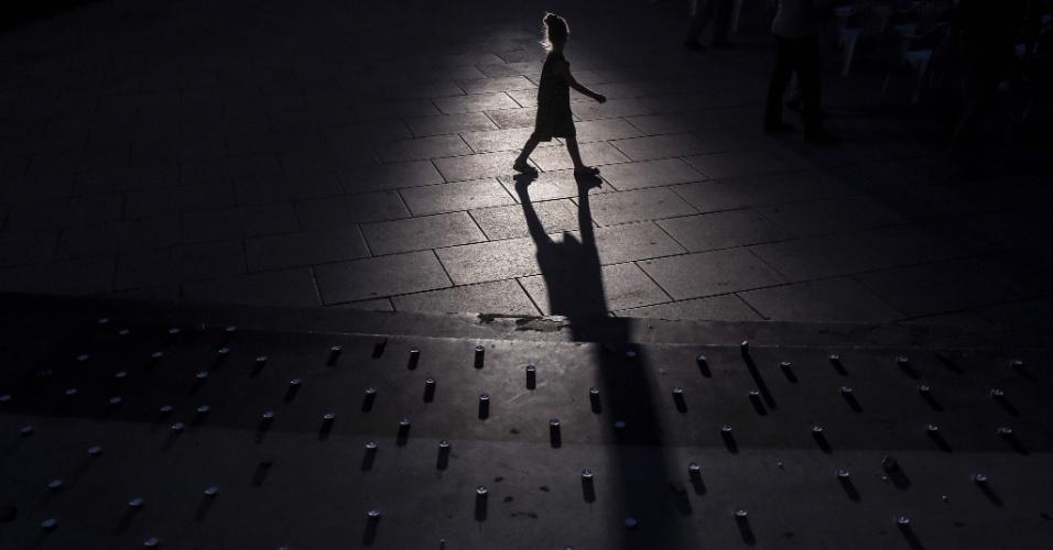 24.jul.2016 - Jovem caminha por velas colocadas em Pristina, capital do Kosovo, em homenagem às vítimas do atentado no shopping center Olympia, em Munique, na Alemanha. Dos nove mortos pelo atirador, três eram albaneses de Kosovo