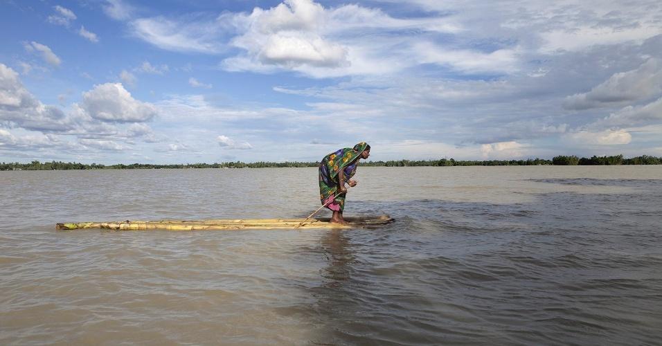 """Em Bangladesh, uma mulher afetada por uma enchente utiliza uma espécie de canoa para chegar a algum local seco para se abrigar. A diretora do programa """"Your Shot"""" da National Geographic. Monica Corcoran, diz que a foto tem uma """"qualidade épica e fala de algo maior do que ela mostra"""""""