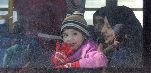 Criança acena de um ônibus usado para a retirada de civis da região leste de Aleppo - Abdalrhman Ismail/ Reuters