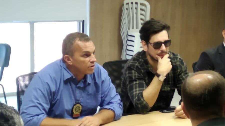 De óculos escuros, o ator João Vicente, do Porta dos Fundos; ao lado, de azul, secretário de Polícia Civil, Marcus Vinícius Braga - Igor Mello/UOL