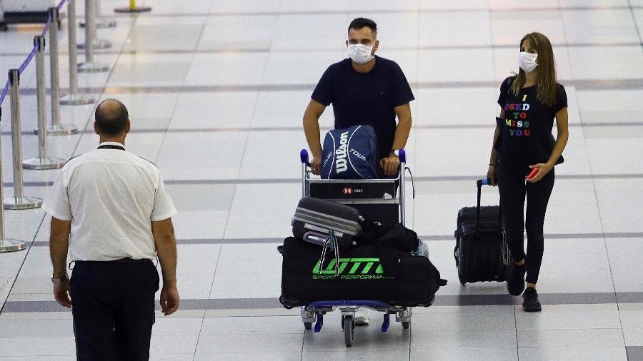 Passageiros com máscaras de proteção contra coronavírus caminham em aeroporto - MATIAS BAGLIETTO
