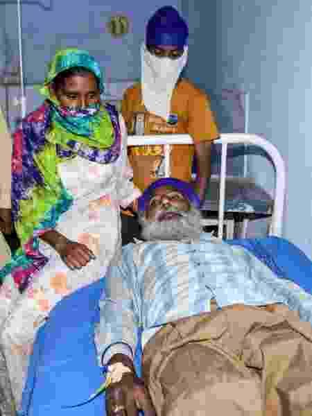 Familiares junto a paciente em hospital de Tarn Taran, na Índia, após supostamente ter ingerido álcool clandestino - Narinder Nanu/AFP