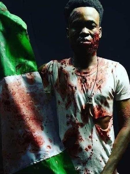 Manifestante posa com a bandeira da Nigéria manchada de sangue - Reprodução/WhatsApp