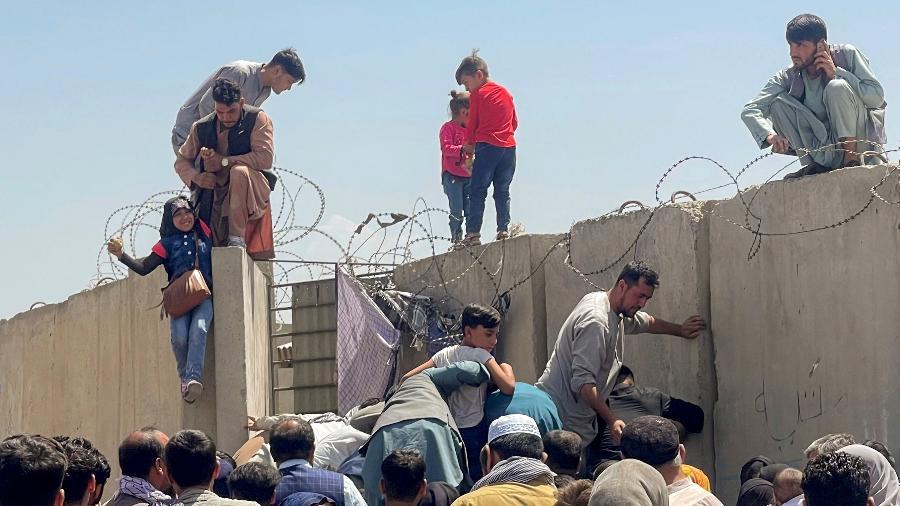 16.ago.2021 - Homem puxa uma criança para dentro dos muros do aeroporto internacional de Cabul, Afeganistão - Stringer/Reuters