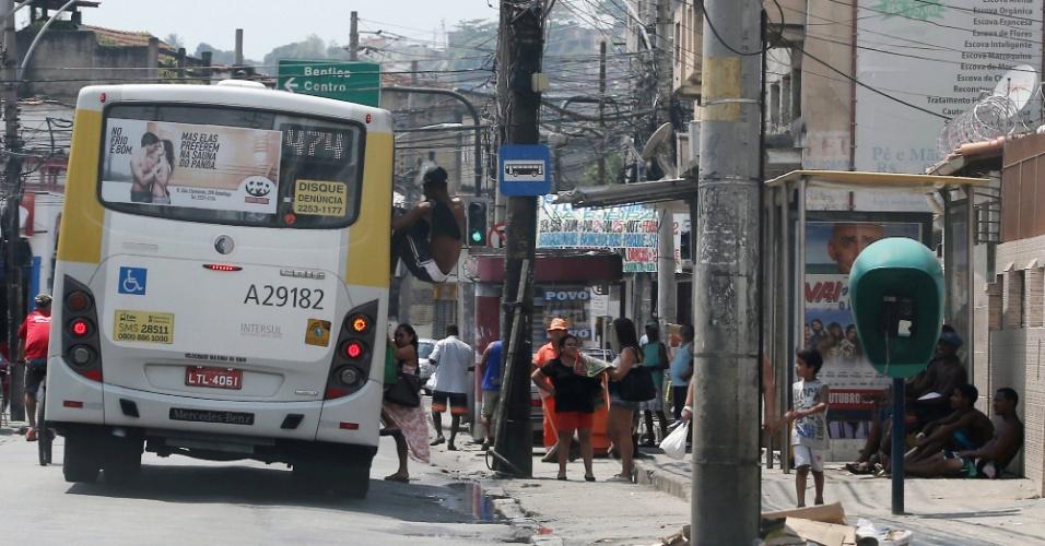 27.set.2015 - Jovem entra pela janela em ônibus na rua Ana Neri, em Benfica, na zona norte do Rio, neste domingo (27). Momentos depois, policiais militares entraram no veículo e retiraram do ônibus o rapaz, que teve de seguir o caminho a pé. A PM reforçou o policiamento no subúrbio e no acesso às praias do Rio depois de uma onda de arrastões