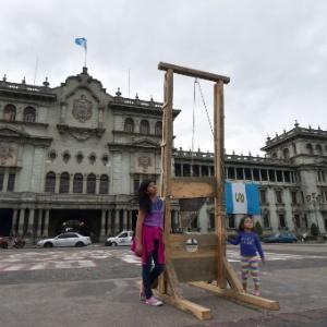 7.set.2015 - Crianças posam para foto ao lado de guilhotina colocada como protesto diante de palácio presencial na Cidade da Guatemala - Rodrigo Arangua/AFP