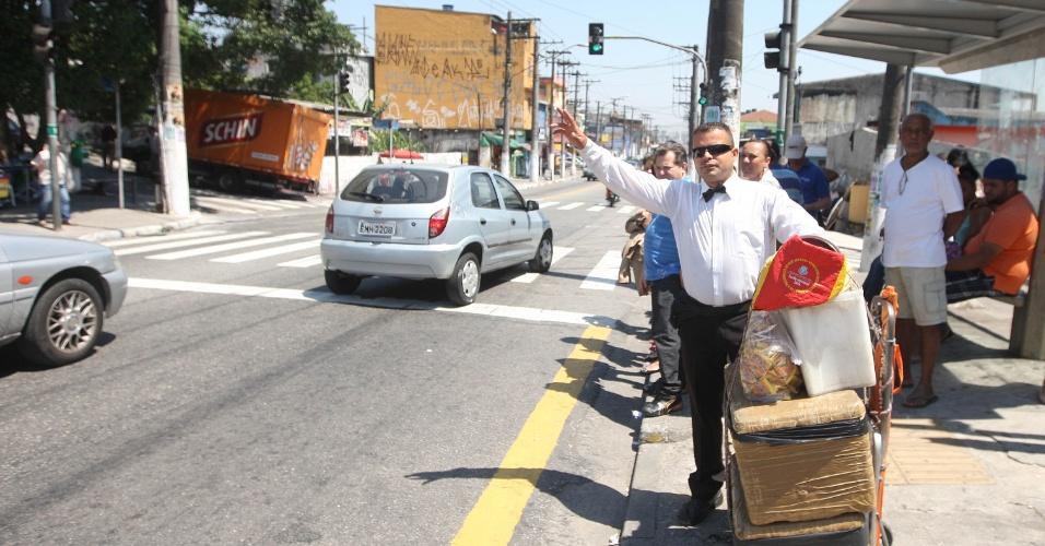 15.out.2015 - Jairo de Freitas chama o ônibus que vai levá-lo ao ponto onde vende garrafas de água