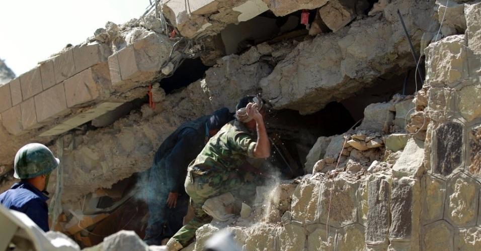 18.jan.2016 - Equipes de resgate retiram vítimas de escombros da sede da polícia em Sanaa, capital do Iêmen, atingida por bombardeio liderado por forças sauditas. Ao menos 22 pessoas morreram