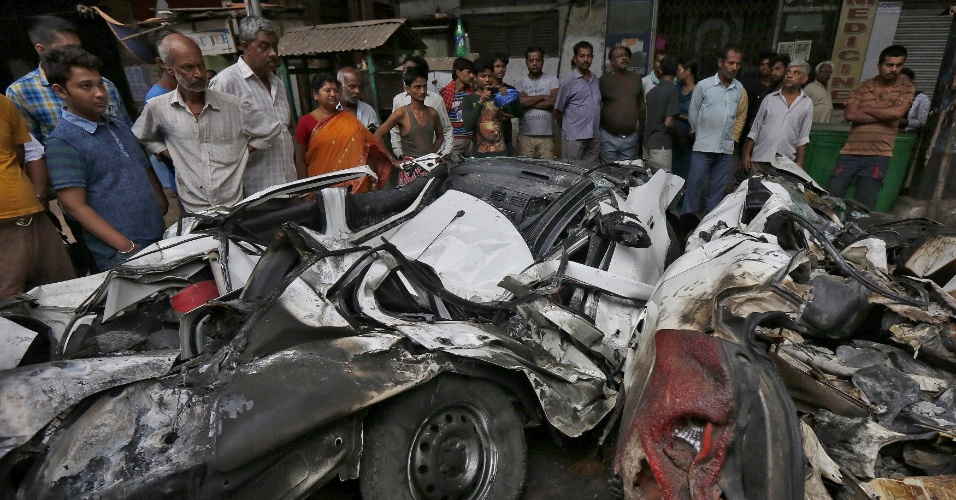 1º.abr.2016 - Curiosos observam o que sobrou de carro que foi esmagado pelo viaduto que desabou na tarde desta quinta-feira (31) em Calcutá (Índia). Dezenas de pessoas permanecem soterradas - as autoridades não precisam o número de vítimas - e ao menos 25 pessoas morreram na queda da estrutura