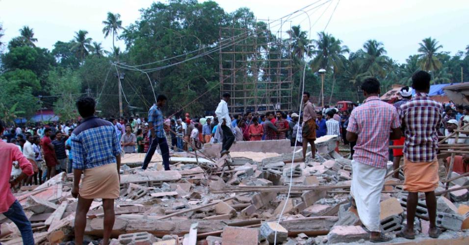 10.abr.2016 - Curiosos passam pelos escombros do incêndio de grandes proporções que atingiu um templo hindu em Kollam, no sul da Índia, e que deixou pelo menos cem mortos, segundo as autoridades locais. Uma multidão estava reunida para uma queima de fogos de artifício pelo ano novo hindu, quando uma faísca acabou provocando uma explosão. A tragédia deixou ainda cerca de 350 pessoas com ferimentos