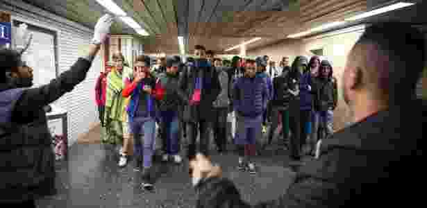 Voluntários direcionam refugiados que chegam à estação de trem de Dortmund, na Alemanha - Gordon Welters/The New York Times