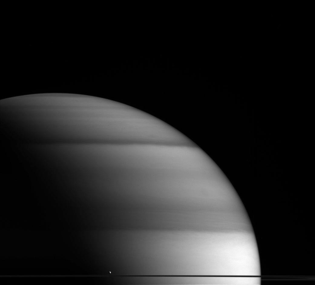 """3.mai.2016 - Encélado é a sexta maior lua de Saturno e possuiu um oceano de água em estado líquido sob sua superfície gelada. Na imagem, feita pela nave espacial Cassini, Encélado aparece em cima dos anéis, como se estivesse """"sentando"""" em Saturno. Antes da nave chegar perto do planeta, os astrônomos acreditavam que a lua era congelada e sem atividades. Porém, as imagens mostraram que Encélado exibe uma notável atividade geológica e tem plumas saindo de sua superfície. Essas plumas são compostas principalmente de vapor da água, que sai da camada de água líquida debaixo de sua concha de gelo, e também contém algumas partículas de poeira"""