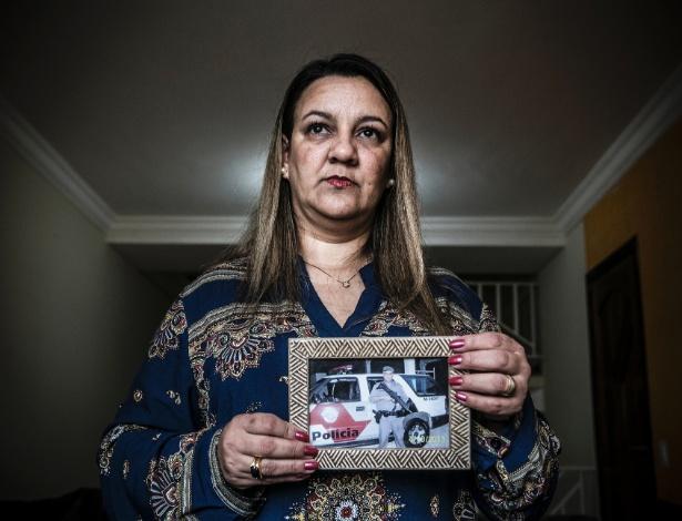 A dona de casa Edirene Alves da Silva Weigert, 47, mostra retrato de seu marido, Swamy Welder Weigert, morto em serviço em Embu das Artes, em 2014