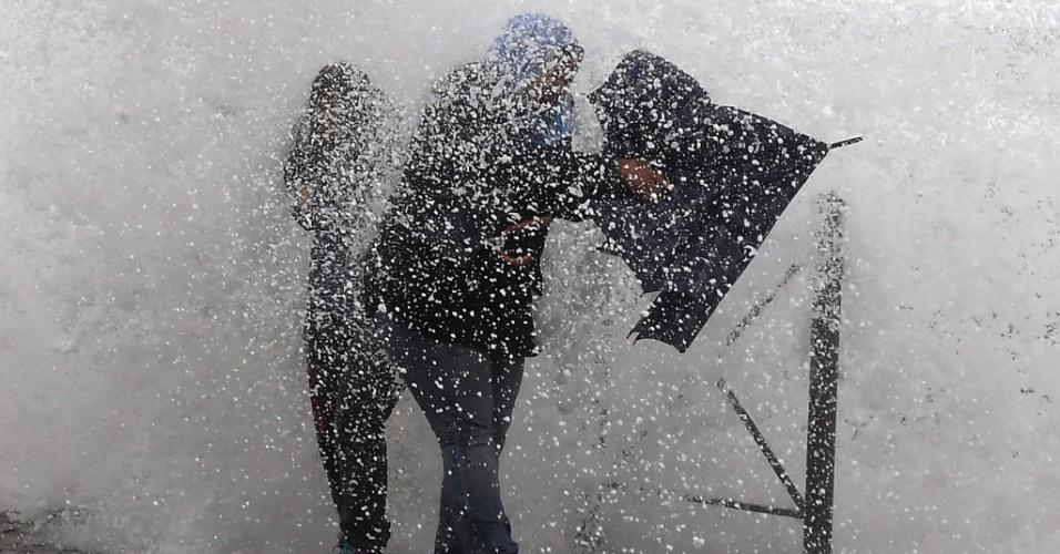 13.out.2016 - Onda atinge rua do porto de Sète, no sul da França, enquanto pessoas andam pelo local chuvoso