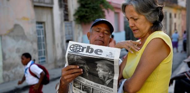 Cubanos leem jornal com capa sobre a vitória de Donald Trump em rua de Havana
