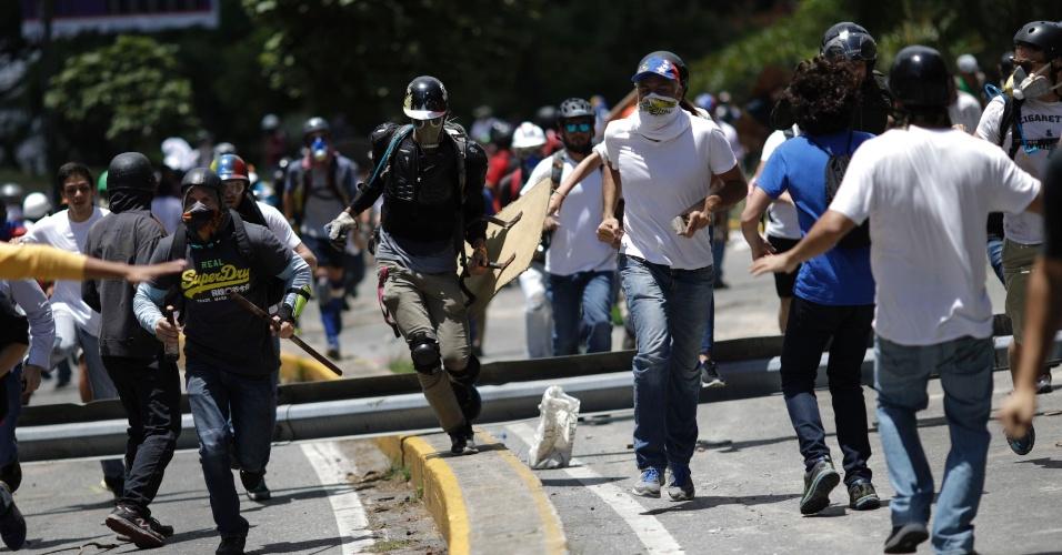 30.jul.2017 - Manifestantes correm durante confronto com forças de segurança