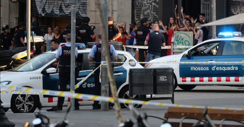17.ago.2017 - Pessoas deixam restaurante com as mãos para cima em inspeção policial momentos depois do ataque com uma van que deixou vítimas na região central de Barcelona