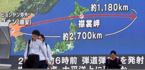 Pedestres passam diante de tela com mapa da península coreana (esq.) e o Japão mostrando a trajetória do míssil lançado pela Coreia do Norte - Kazuhiro Nogi/ AFP