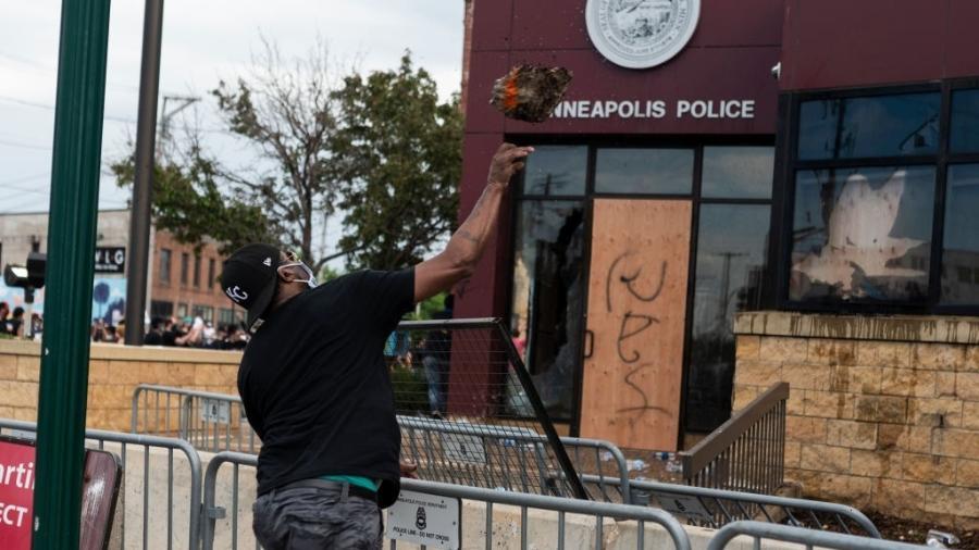 Manifestante arremessa pedaço de pedra em delegacia da polícia de Minneapolis, nos EUA, após a morte de George Floyd - Stephen Maturen/Getty Images