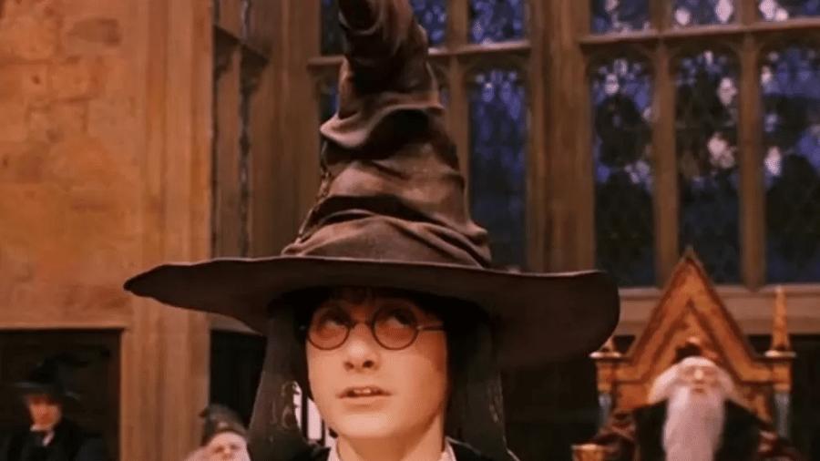"""Harry Potter usa o chapéu seletor em Hogwarts em cena do filme """"Harry Potter e a Pedra Filosofal"""" - Reprodução"""