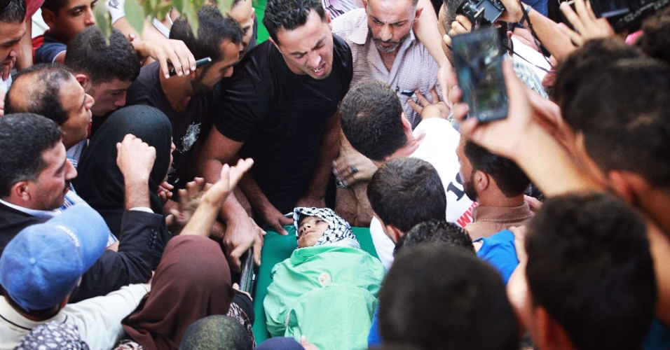 5.out.2015 - Parentes velam o corpo de Abdel Rahman Abdullah, de 13 anos, morto por militares israelenses em um campo de refugiados próximo a Belém, na Cisjordânia. O adolescente foi o segundo palestino morto por soldados de Israel em 24 horas, numa escalada de violência iniciada após o assassinato de quatro israelenses por palestinos.