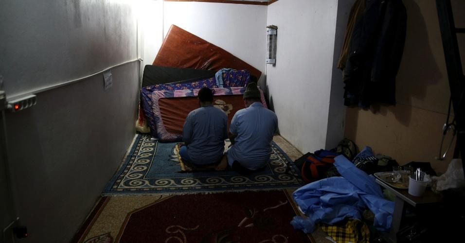 Muçulmanos, médicos rezam em espaço dentro do hospital improvisado na cidade de Douma, na Síria. Os feridos civis são levados para estas bases e abrigos transformados provisóriamente em hospitais onde médicos e voluntários trabalham em condições precárias