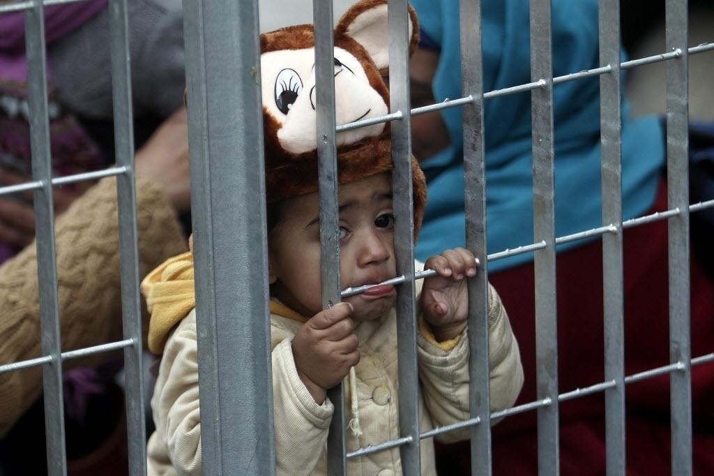 30.dez.2015 - Criança afegã morde a grade de um acampamento improvisado para refugiados em Atenas, na Grécia. Mais de 1 milhão de imigrantes chegaram por meio de rotas marítimas à Europa neste ano, segundo o Alto Comissariado das Nações Unidas para Refugiados. De acordo com o relatório, 844.176 pessoas chegaram à Grécia, usando a rota do mar Egeu