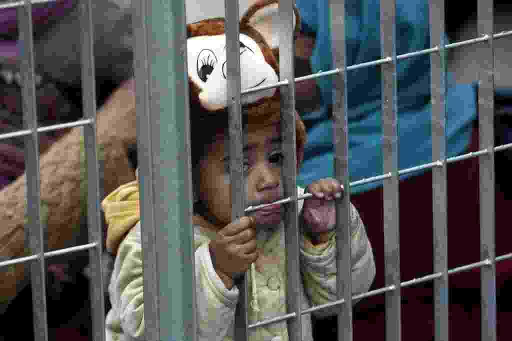 30.dez.2015 - Criança afegã morde a grade de um acampamento improvisado para refugiados em Atenas, na Grécia. Mais de 1 milhão de imigrantes chegaram por meio de rotas marítimas à Europa neste ano, segundo o Alto Comissariado das Nações Unidas para Refugiados. De acordo com o relatório, 844.176 pessoas chegaram na Grécia, usando a rota do Mar Egeu - Alexandros Vlachos/ EFE